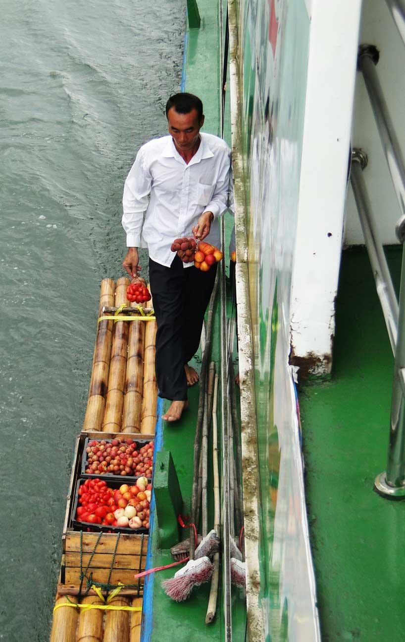Vendedor de frutas junto a un crucero del río Li.